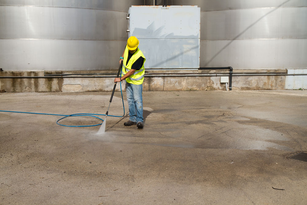 man washing concrete